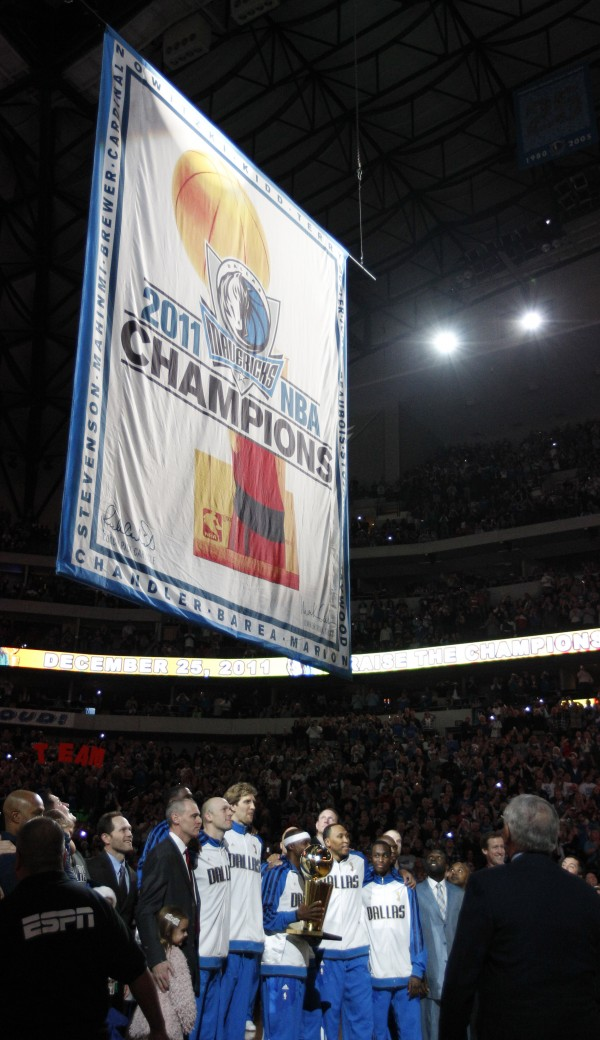 The Dallas Mavericks line up as the championship banner is raised before an NBA basketball game against the Miami Heat in Dallas on Sunday, Dec. 25, 2011.