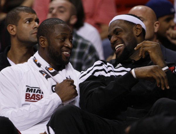 Miami Heat guard Dwyane Wade (left) and forward LeBron James share a laugh on the bench during the second half of an NBA preseason basketball game against the Orlando Magic, in Miami.