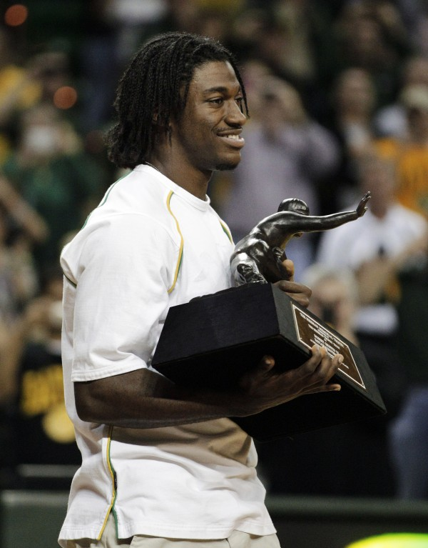Baylor quarterback and Heisman Trophy winner Robert Griffin III walks onto the basketball court holding the trophy during a halftime ceremony of an NCAA college basketball game between Baylor and Bethune-Cookman, Wednesday, Dec. 14, 2011, in Waco, Texas.