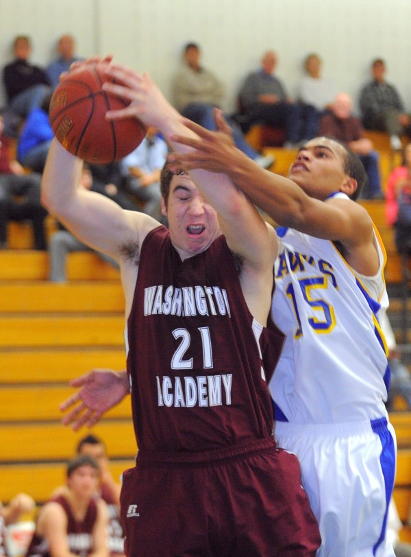 Washington Academy's Drew Sansing (left) takes a rebound over Hermon High School's Fritz Marseille during the first half of the game in Hermon on Wednesday evening.