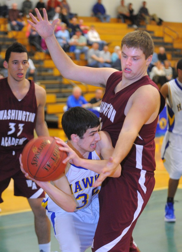 Hermon High School's Nate Matthews (left) looks up to pass the ball as Washington Academy's Tyler Warner defends during the first half of the game in Hermon on Wednesday evening.