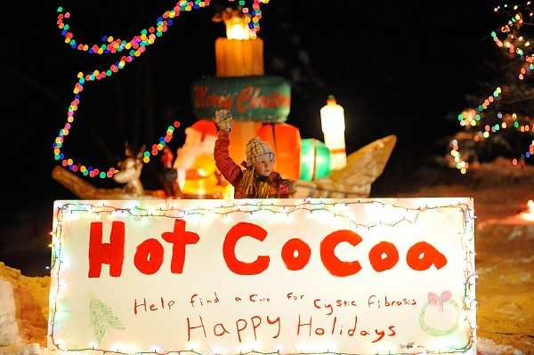 Abby Sargent holds up the family's billboard offering passing motorists free hot chocolate in front of her Brewer home in December 2010.