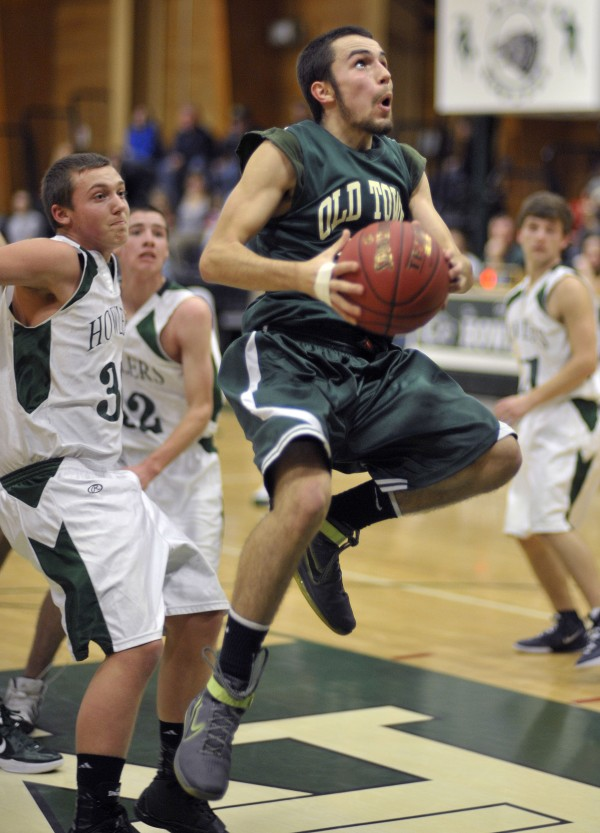 Old Town boy's player Matt Melanson (32) won't be denied as he leaps for the hoop past Howland's Wade Thurlow (33) in the first half of their preseason game in Howland on Tuesday, Nov. 29, 2011.