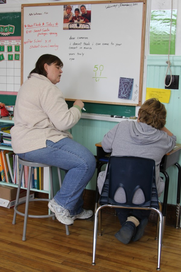 "Education technician Lisa Turner helps fourth-grader Alex Tully, 9, correct his math test. Turner graduated from the K-8 school in the 1970s. In her day, there were 15 kids in the 100-year-old, one-room schoolhouse. Now there are three. In an effort to attract more young families to move to the island and enroll their children in the school, the town is building affordable rental homes. One problem, Turner said, is that children who go through the school together rarely get married when they grow up. ""You're more like cousins than schoolmates,"" she said. ""You don't marry your cousin."""