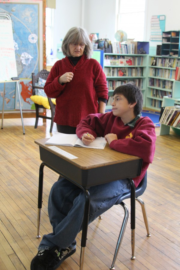 Paula Greatorex, the teacher at Isle au Haut's one-room schoolhouse, helped fifth-grade student Andrew Barter, 12, last week. Andrew is one of three students who attend the island school. In an effort to attract more young families to move to the island and enroll their children in the school, the town is building affordable rental homes.
