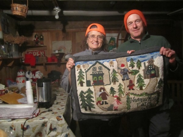 Nancy and Len Price in the warming room of their barn, soon to be filled with customers looking for hot cider after picking out their Christmas trees.  They are  holding a rug hooked by a friend, depicting Nutkin Knoll Farm.
