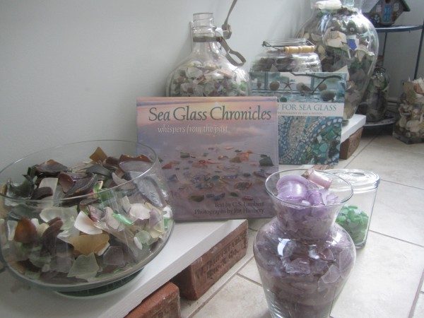 A selection of Bill and Helen Carney's sea glass collection, with some of their books about the world of sea glass.