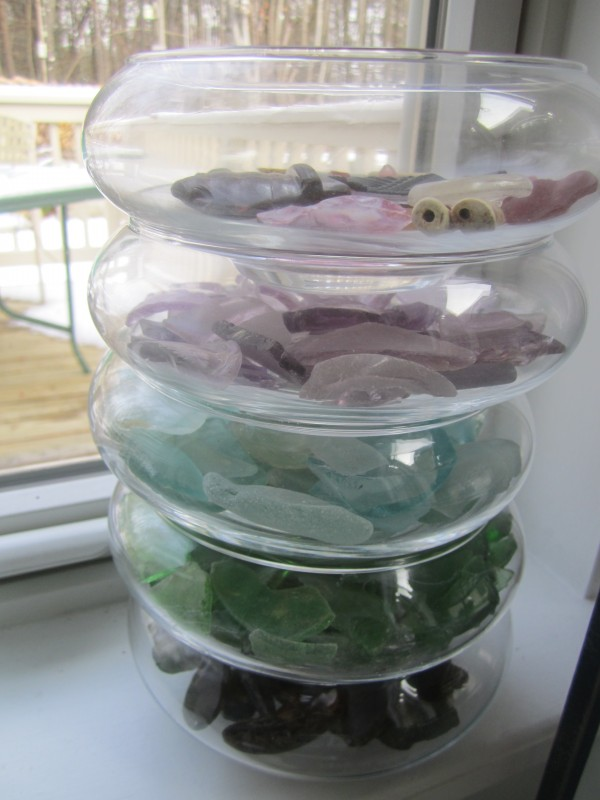 An artistic display of layered sea glass, sorted by color.