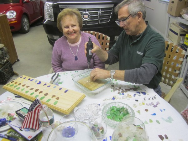 Helen and Bill Carney sit at Bill's worktable while he drills a hole in a piece of sea glass for a bracelet.