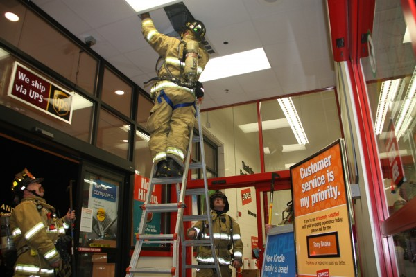A firefighter reaches into the ceiling to check an electric heater motor at about 7:50 p.m. Wednesday after the Rockland Fire Department was called to address a report of smoke at the Staple's store on Camden Street. The store was evacuated, but reopened within an hour after firefighters shut off power to the malfunctioning heater.