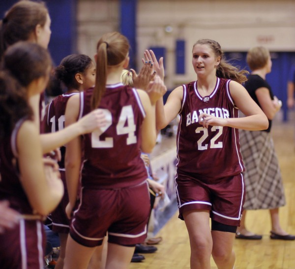 Bangor's Kristen Henigan (22) gets the hand-slap of approval from her teammates as she is substituted out for a break in their game against the  Medomak Valley girls team in preseason action at the Bangor Auditorium on Saturday, Nov. 26, 2011.