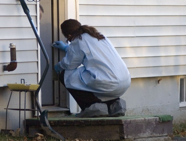 A Maine State Police reconstruction team takes samples, Tuesday , Dec 20, 2011, from the edge of the doorway in to the home where, on Dec. 16, 20 month-old Aysha Reynolds was last seen on Violette Avenue in Waterville, Maine.