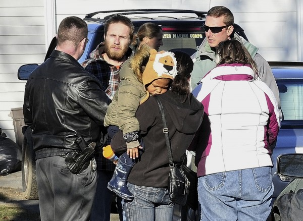 In this Sunday, Dec. 18, 2011 photo, Maine State Police Det. Christopher Tupper, left, and Waterville Det. Lincoln Ryder, right, question Justin DiPietro, second from left, after he arrived at his home in Waterville. Police were searching his home and the surrounding neighborhood for his missing 20- month-old daughter Ayla Reynolds.