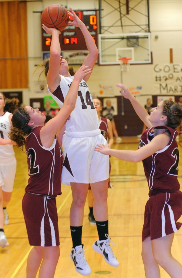 Nokomis Regional High School's Marissa Shaw (center) goes up for a shot between Maine Central Institute's Katherine Smedberg (left) and Brianna Losee during the first half of the game in Newport on Friday evening.