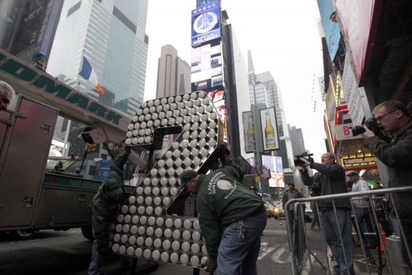 "Employees with the the Landmark Sign group carry a seven-foot-tall numeral ""2"" in New York's Times Square, Wednesday, Dec. 21, 2011. The world-famous ""2"" will make the New Year complete in the ""2-0-1-2"" sign as the Times Square New Year's Eve Ball descends from high atop One Times Square on Dec. 31."