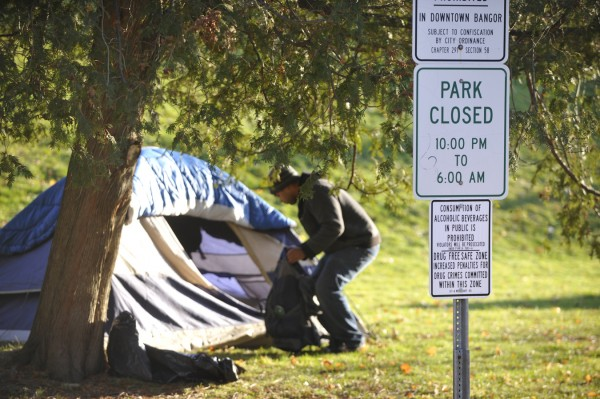 A member of the Occupy Bangor encampment organizes his belongings in front of his tent Monday morning, Dec. 5, 2011, after relocating the tent to Peirce Park in downtown Bangor.