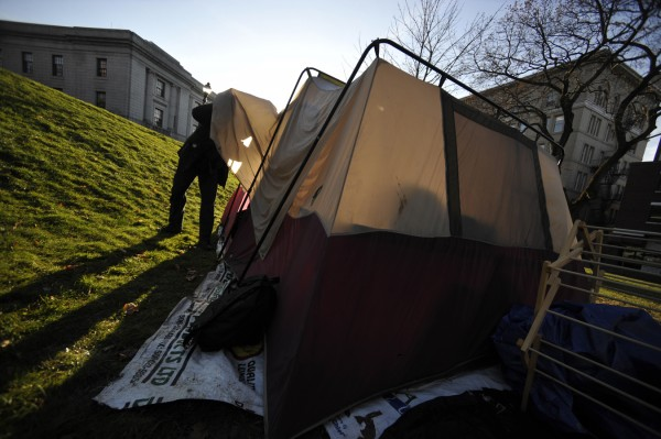 Conrad Cook, a member of the Occupy Bangor encampment, looks inside one of the group's tents that they decided to move to Peirce Park across the street from Bangor City Hall.