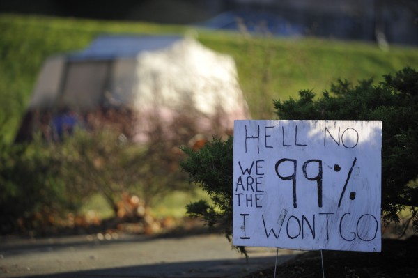 A protest sign remains in Peirce Park against the backdrop of one of several Occupy Bangor tents that were moved there from the Bangor Public Library grounds over the weekend.