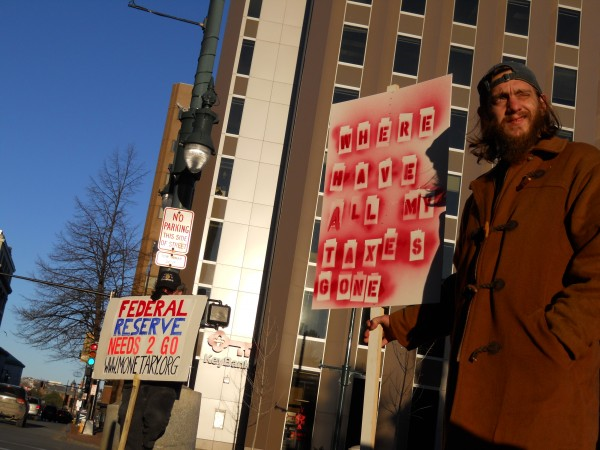 Matthew Coffey (right) is among those holding signs in acknowledgement of OccupyMaine's two months in Portland recently in Monument Square. The city denied a permit late Wednesday for the group to camp in nearby Lincoln Park.
