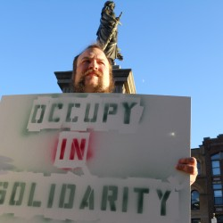 John Schreiber holds a sign supporting OccupyMaine on Thursday afternoon in Monument Square.
