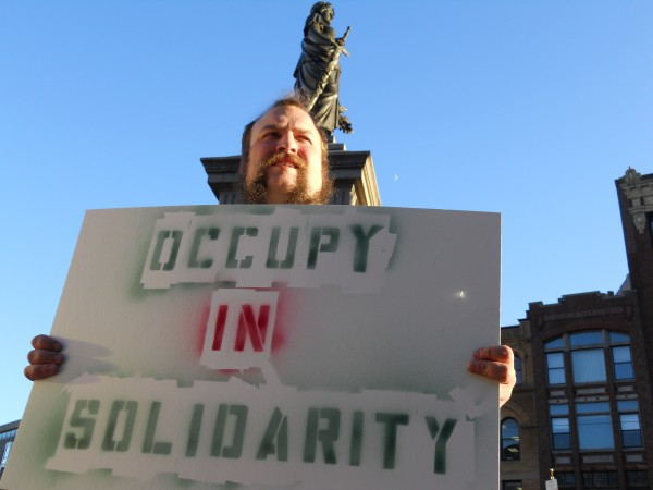 John Schreiber holds a sign supporting OccupyMaine on Thursday afternoon in Monument Square. Thursday marked the movement's second month in Portland.
