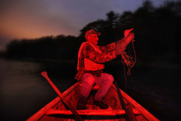 Andy Guerette, 59, sets a duck decoy near a tidal marsh on the Kennebec River before dawn. A red filter was placed over my flash to mimic the red-filtered headlamp Andy's son was using to preserve his night vision.