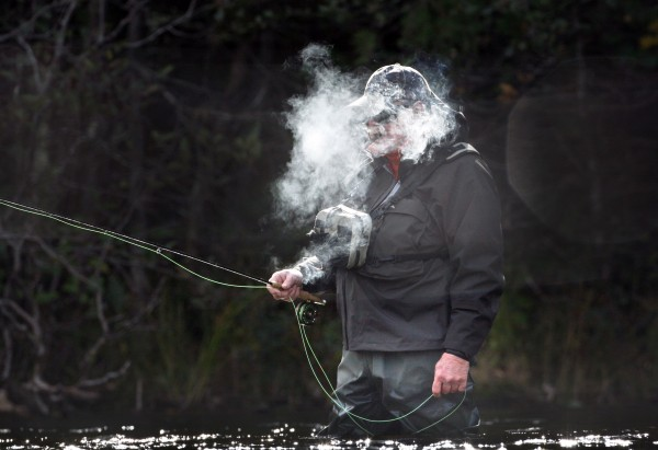 Lou Savlen of Lexington, Mass., puffs on a cigar while fishing at Grand lake Stream on Oct. 11. There was something about his head being lost in a cloud of smoke that I liked. But the picture just didn't fit in with the more colorful photos of fishing during the fall foliage season.