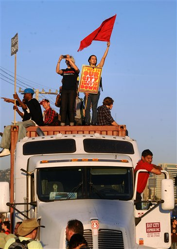 In this Nov. 2, 2011, occupy Oakland protester Alfredo Coronado waves a flag while standing atop a big rig truck at the Port of Oakland in Oakland, Calif. Protesters want to shut down ports up and down the U.S. West Coast on Monday, Dec.12,2011, to gum up the engines of global commerce. But organizers who are partly billing this effort as a show of solidarity with longshoremen have not won the support of the powerful union representing thousands of dock workers.