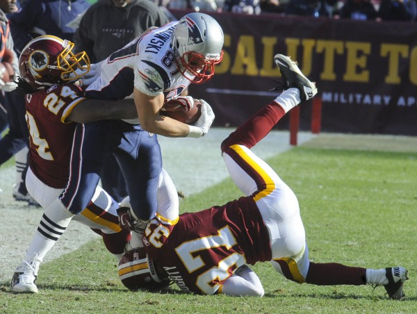 New England Patriots tight end Rob Gronkowski (center) fights with Washington Redskins strong safety DeJon Gomes (24) and free safety Reed Doughty (37) during the first half of an NFL football game on Sunday, Dec. 11, 2011, in Landover, Md.