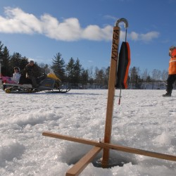A tip-up sits on a freshly drilled ice hole on Pickerel Pond during Maine Youth and Fishing Association's annual ice fishing day off Stud Mill Road near Greenfield in January 2010.