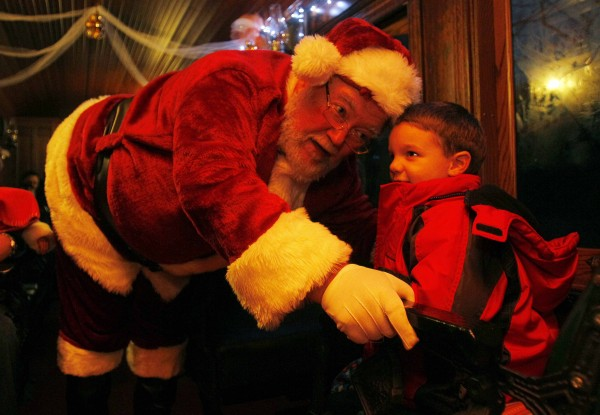 Santa listens to Andrew Greene, 4, of Freeport whisper what he wants for  Christmas while riding the Polar Express at the Narrow Gauge Railroad in Portland.
