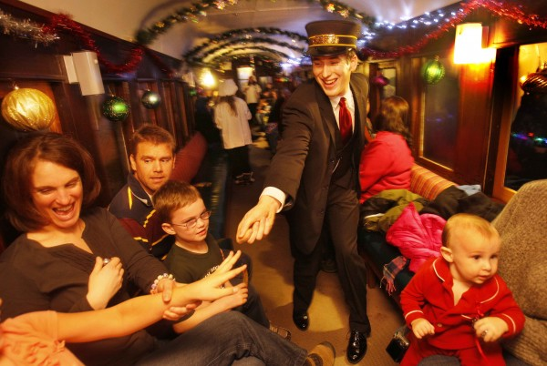 Conductor Jeff Ferland reaches for a youngster to dance with while holiday music plays on the Polar Express at the Narrow Gauge Railroad in Portland.