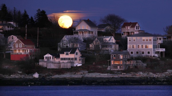 The full moon rises behind Bay Point in Georgetown, on the east side of the Kennebec River in this photo made with a telephoto lens from Popham Beach State Park, Saturday, Dec. 10.
