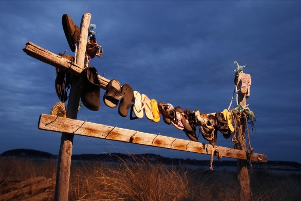 Warm weather beach footwear is displayed along a walkway through the dunes in Phippsburg.