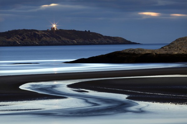 The incoming tide swirls over the beach in this two-minute time-exposure made by the light of the full moon at Popham Beach State Park, Sunday, Dec.11. Sequin Island light shines in the distance.