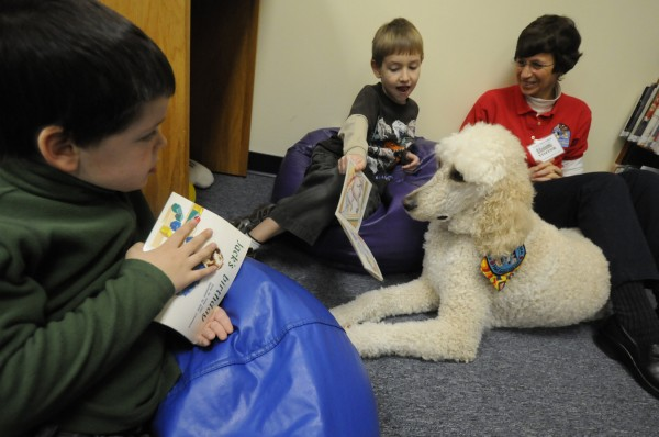 "Xander Watkins, 7, shows an illustration from the children's book ""Are You A Bookworm?"" to Miguel, a therapy and reading dog, as Miguel's owner, Renee Garrett, of Holden and first grade classmate, Drew Heber (left), 7, look on."