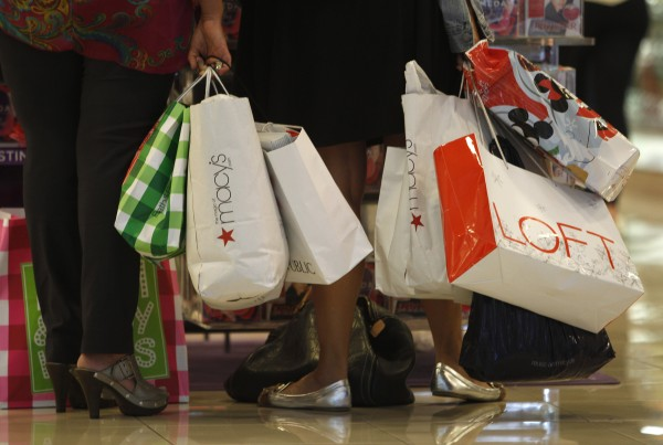 In this Nov. 25, 2011 file photo, shoppers stop to look at a display while shopping at Dadeland Mall, in Miami. Americans spent more on autos, furniture and clothing last month as retail sales rose for the sixth straight month.