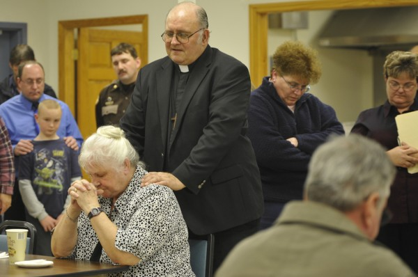 The Rev. Stephen Dean, pastor of the United Methodist Churches in Guilford and Ripley, his wife, Glenna Dean (bottom left), and other friends and family of Udo Schneider bow their heads in prayer as they remember the man who touched their lives during a celebration of Schneider's life at Mount Kineo Masonic Lodge in Guilford Tuesday afternoon, Dec. 6, 2011.