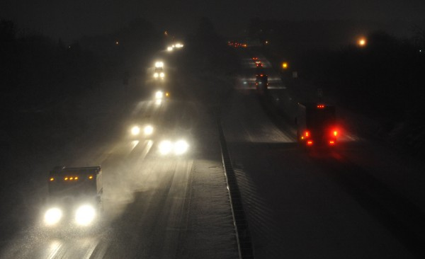 Pre-dawn traffic moves slowly but steadily on I-95 during Friday morning's fresh snowfall in Bangor. Northward view from Bangor's Essex Street overpass.