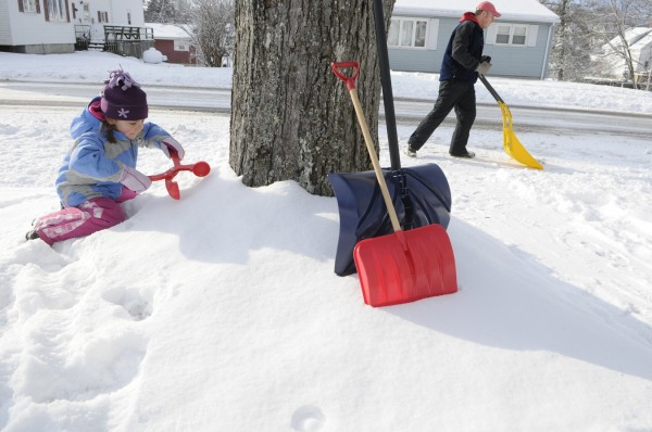 Maggie Metzler, 4, scoops up some freshly fallen snow with one of her Christmas gifts — a snowball maker — as her dad, Jake Metzler, uses a snow pusher to remove the white stuff from their driveway on Lincoln Street in Bangor on Monday morning, Dec. 26, 2011.