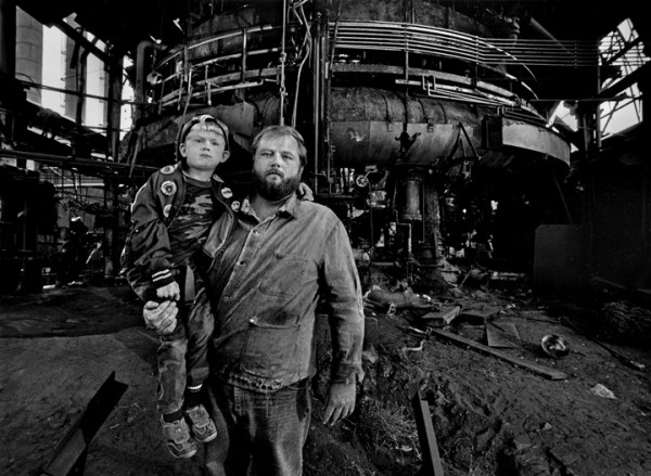 "Ken Platt Jr., with son Ken, in front of the abandoned ""Jenny"" Blast Furnace in Youngstown, Ohio, 1984."