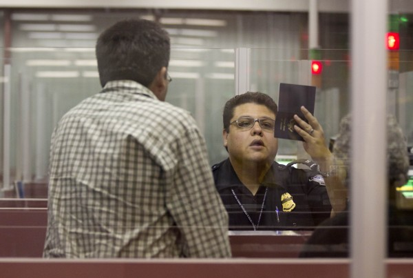 A Customs and Border Protection officer checks the passport of a nonresident visitor to the United States inside immigration control at McCarran International Airport, Tuesday, Dec. 13, 2011, in Las Vegas.