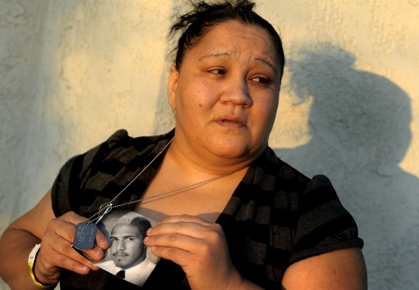 Suzanne Sullivan holds a photo of her son Christopher Sullivan, an Army soldier, outside her home in San Bernardino, Calif., Saturday, Dec. 24, 2011. Sullivan, who survived a suicide bombing last December while serving in Afghanistan, is now in critical condition after a gunman shot him during his homecoming home party Friday in San Bernardino.