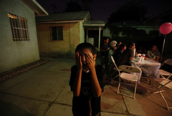 Jese Castillo, 11, covers his eyes as he plays during his birthday party on Sept. 13, 2011, in Los Angeles, California. Jese is autistic and is making progress in his social skills. After spending his 10th birthday party mostly alone, he played with his cousins at his 11th.