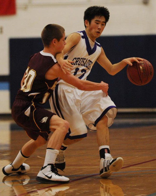 John Bapst's Josh Storgaard loses control of the ball while being guarded by Caribou's Dayne Savage during first period action in Orono on Saturday, Dec. 10, 2011.
