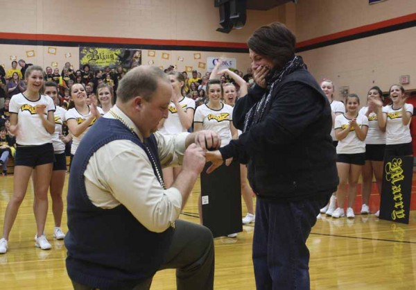 With banners held high, cheerleaders helped Pierre Huntress, at left, propose to his future-wife, Buffy Thibodeau, in between boys and girls varsity basketball games on Dec. 14 at the Limestone Community School gymnasium. Between 700 and 800 people were on hand to cheer as Huntress got down on one knee and placed the engagement ring on Thibodeau's finger.