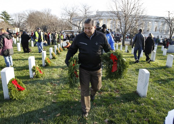 Gov. Paul LePage of Maine volunteers to lay holiday wreaths at the graves of fallen soldiers at Arlington National Cemetery in Washington on Saturday Dec. 10, 2011, during Wreaths Across America Day.