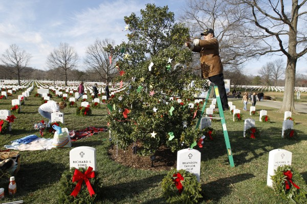 William Duvel decorates a tree over the grave of his stepson, Air Force Scott E. Duffman, at Arlington National Cemetery in Washington on Saturday Dec. 10, 2011, during Wreaths Across America Day.