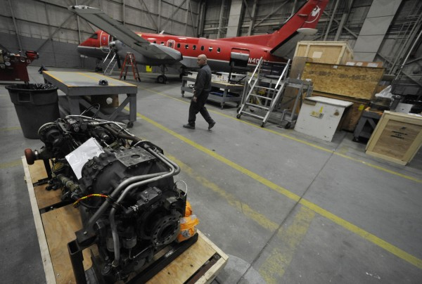 Aaron Bryant of Ellsworth, a spray technician at C&L Aerospace, an international aircraft supplier and maintainer, walks amidst the engines, fuselages and other airplane parts old and new at its Maine office in Bangor Friday afternoon, Dec. 16, 2011.