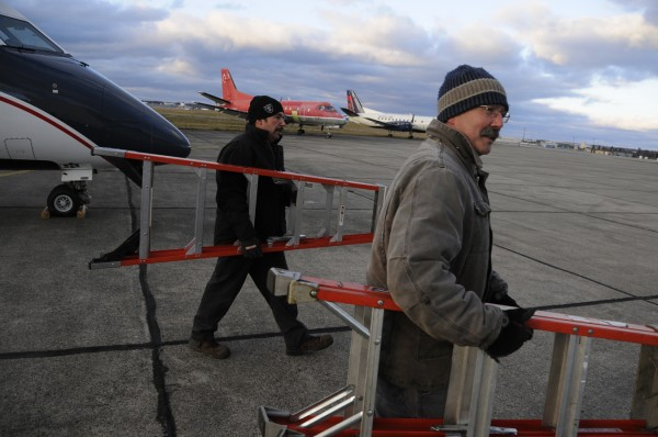 Bill Donahue (right) of Winterport and Scott Macalino of Lincoln, both mechanics at  C&L Aerospace, return to the hanger after attending to aircraft stored on the facility's tarmac Friday, Dec. 16, 2011.